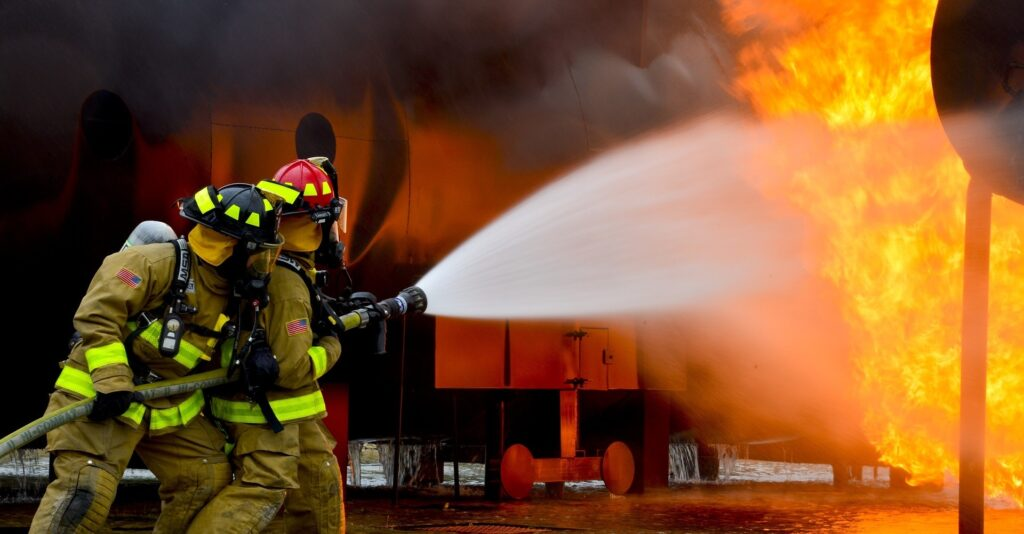 two firefighters fighting blaze with water