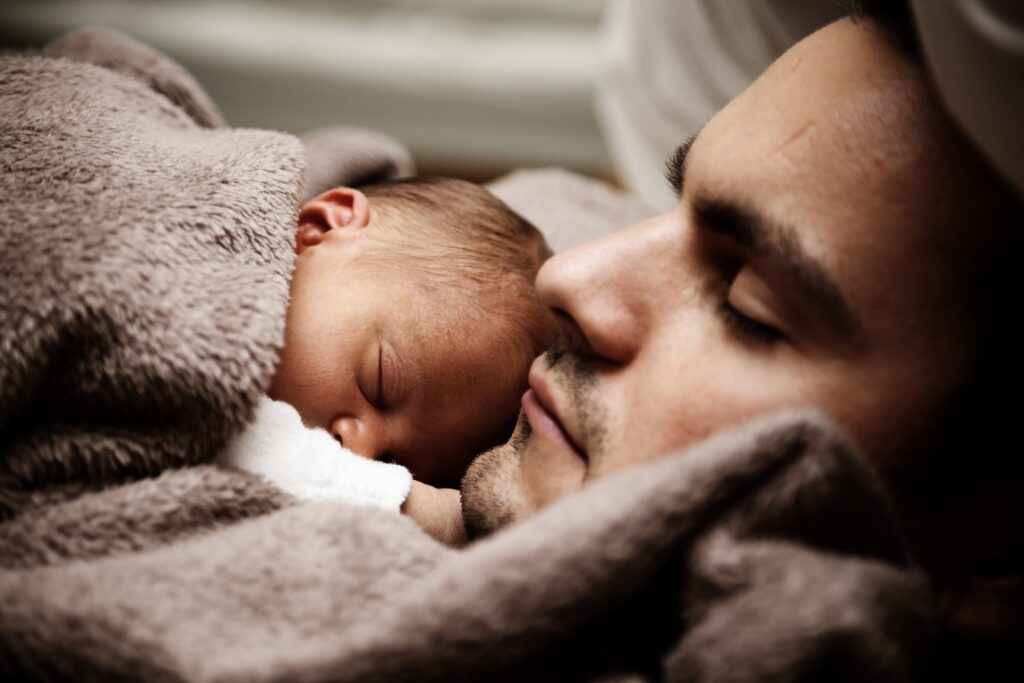 baby sleeping on man's chest