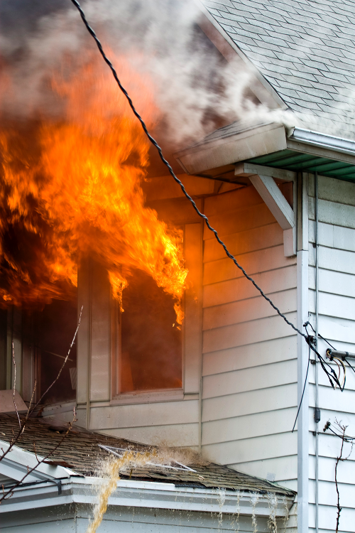 house with white siding and flames coming from window