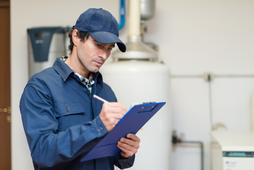 man wearing blue uniform writing inspection notes on clipboard